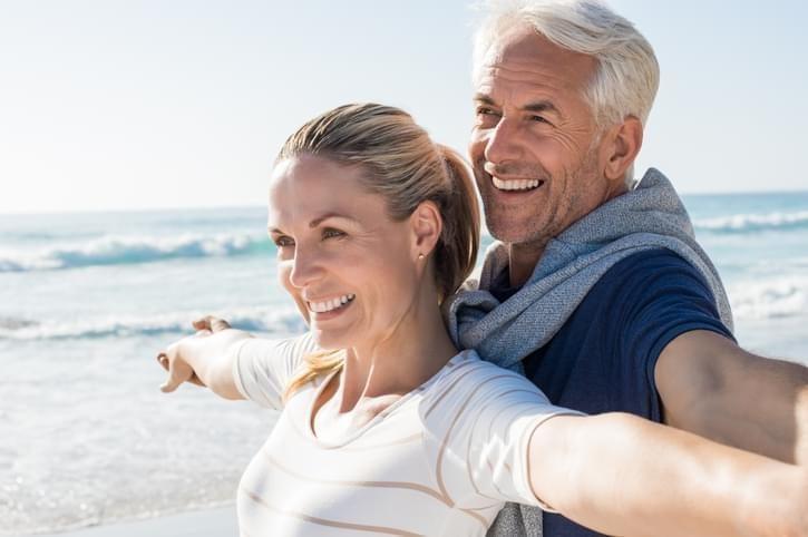 Senior couple smiling on a sunny beach