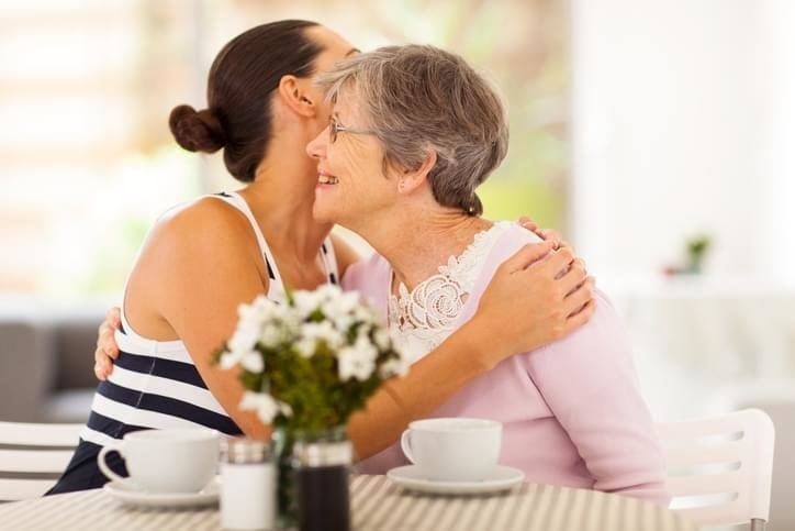 Adult woman hugging her elderly mother