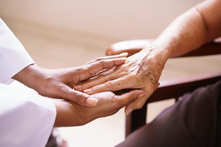 Senior Woman holding hands with hospice doctor