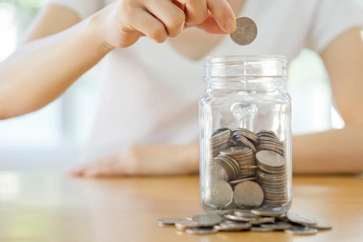 Woman dropping coins into a glass jar