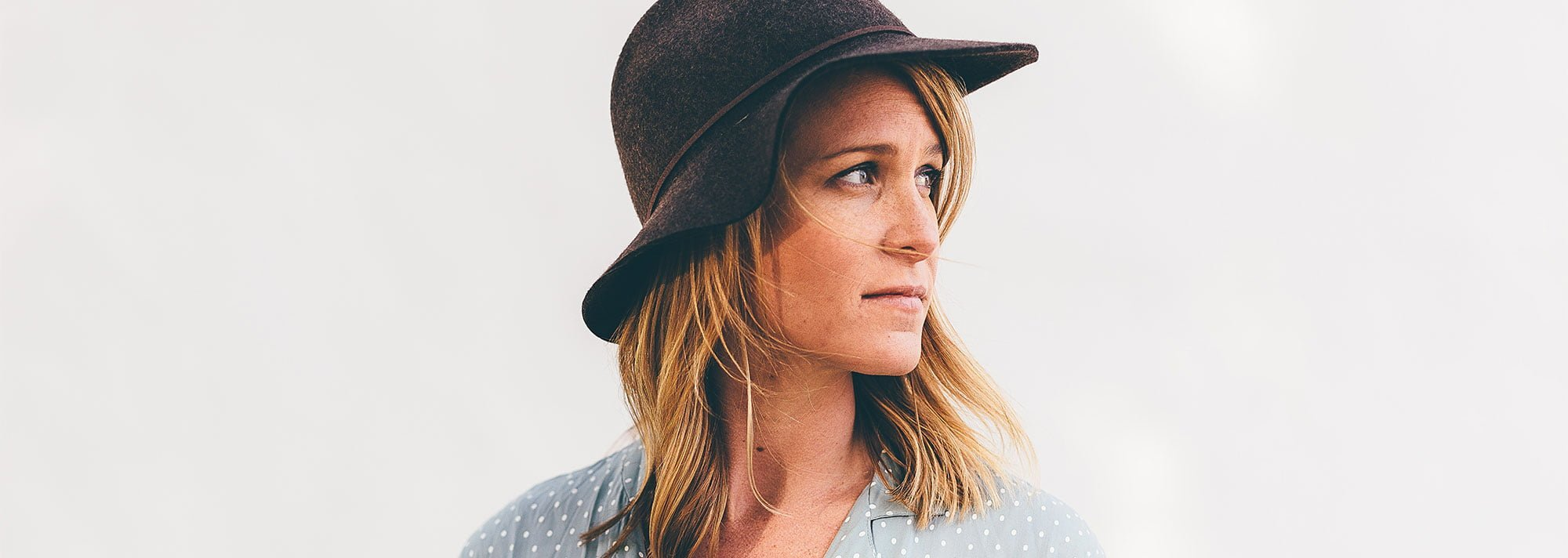 Woman wearing hat looking off into the distance