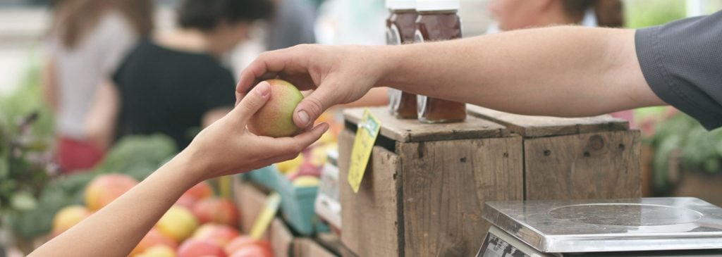 Market stall owner selling apple to customer