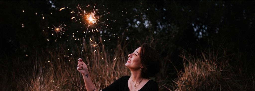Woman playing with sparkler in the dark as she thinks about her future