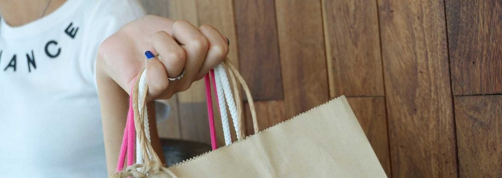 Woman's hand holding bags after going on shopping splurge