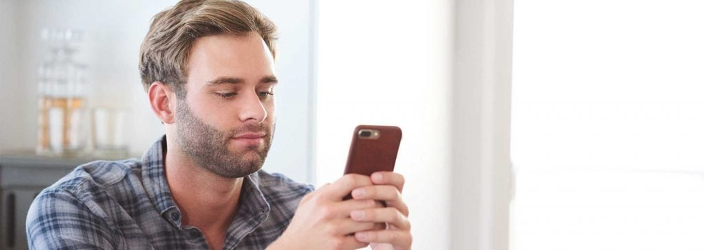 Young man procrastinating by reading on his phone while at work