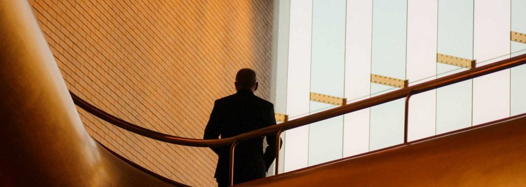 Man in office building looking out window contemplating redundancy