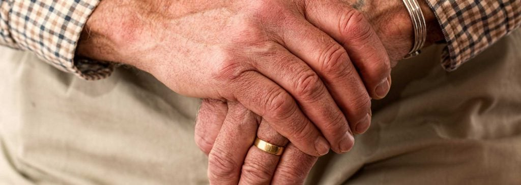 Close up of man's hands on walking cane as he contemplates superannuation death benefits