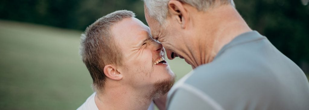 Older man and his son (who has an intellectual disability) laugh as they embrace after receiving good news regarding the NDIS