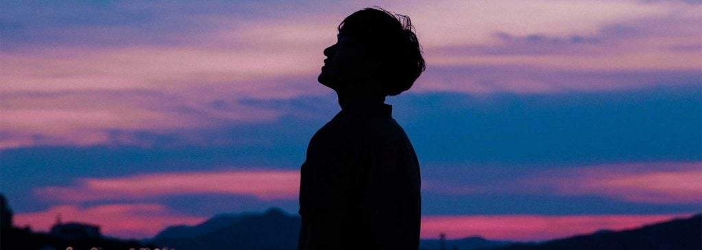 Silhouette of a man standing in front of a pink and purple sunset - representing behavioural analytics