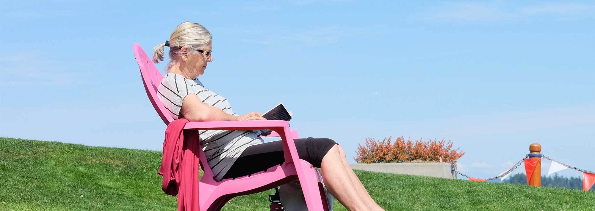Retired woman is able to live the dream by relaxing outside on a pink lawn chair and reading a book
