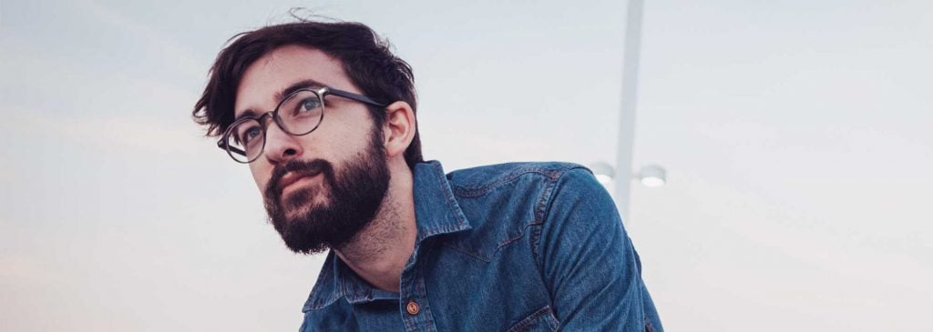 Man with beard and glasses contemplates his company's service offering