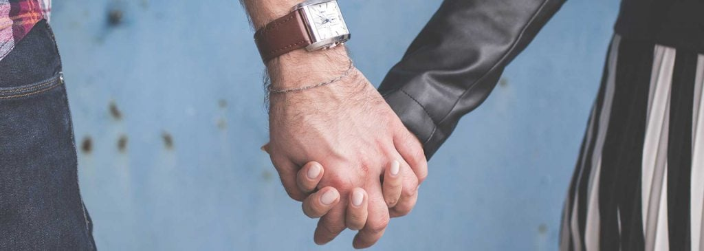 Close up of man and woman holding hands in front of a blue wall as they prepare to see their trusted financial adviser