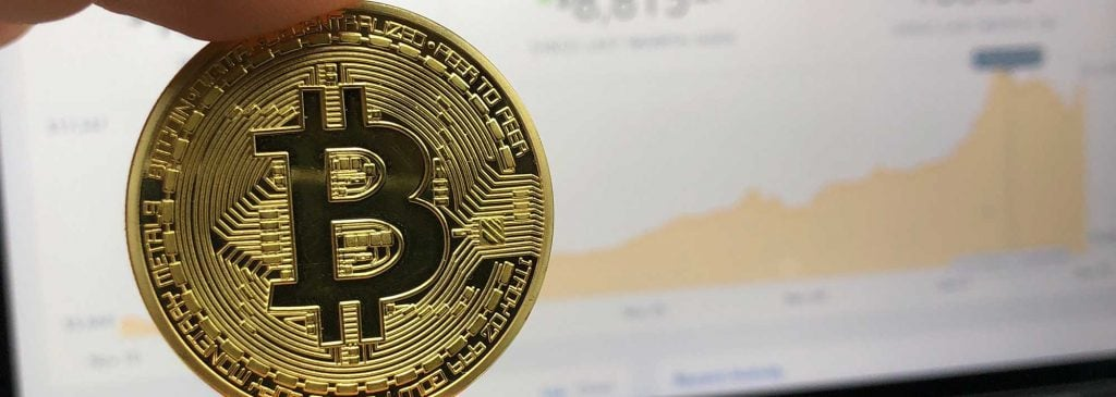 Close up of physical Bitcoin being held in front of computer screen displaying rising value