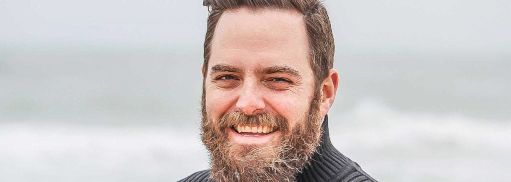 Close up of man with large beard who is planning his early retirement smiling on a beach