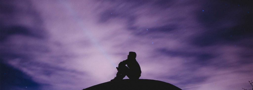 Silhouette of man sitting on hill in front of purple night sky as he contemplates which super fund to choose
