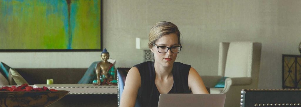 Young businesswoman with glasses sits at her table in her dining room and researches insurance on her laptop