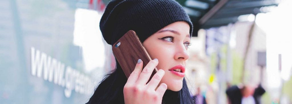 Close-up of woman with beanie who looks like she is experiencing stress is talking on her mobile phone outside