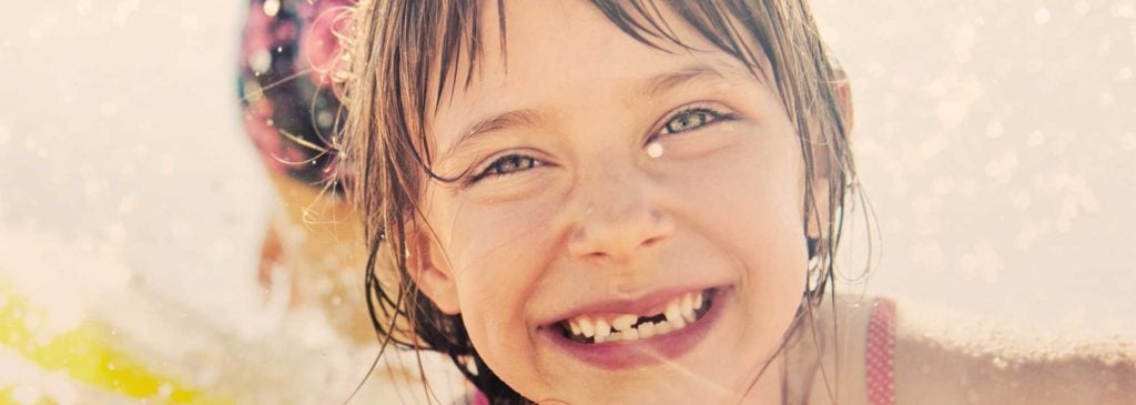Young girl smiling happily with front tooth missing